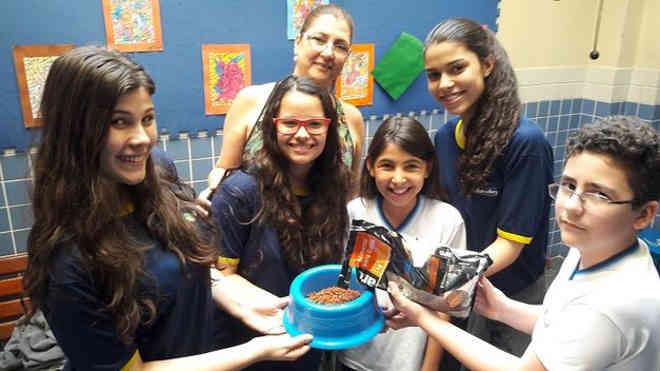 A diretora do Educandário Syllabatim, Valéria Machado, com alunos pela campanha 'Tigela com Ração'.