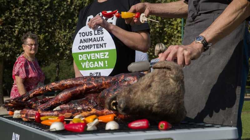 Ativistas da Peta organizam uma ação em frente à Torre Eiffel, onde um cachorro falso é assado em churrasqueira - AFP