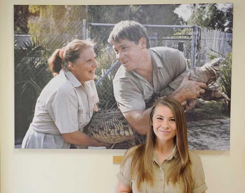 Bindi atualmente diante da foto de Steve Irwin e de sua avó