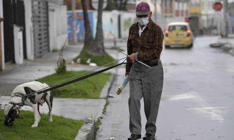 Um homem usa uma máscara facial como medida preventiva contra a propagação do novo coronavírus, enquanto passeava com seu cachorro em Bogotá, em 16 de março de 2020. RAUL ARBOLEDA / AFP (AFP)