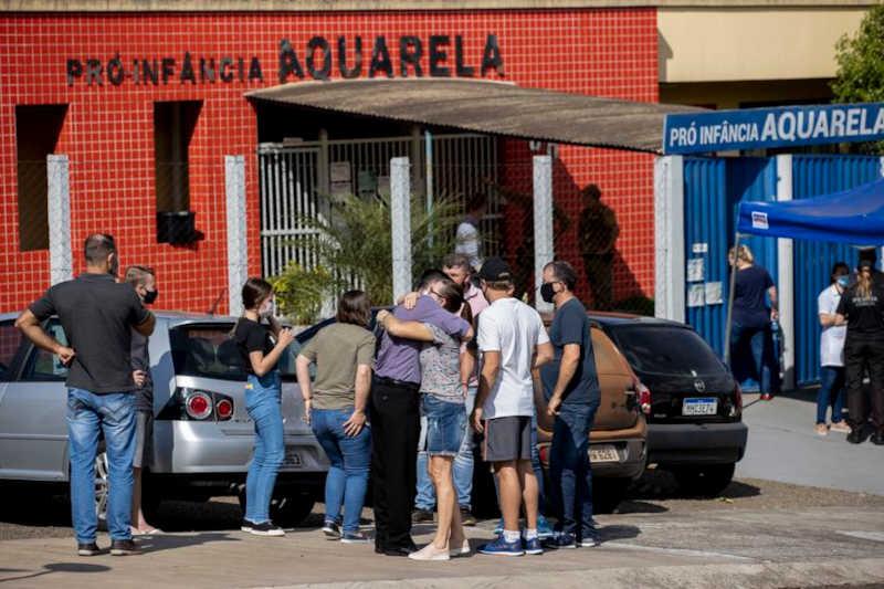 Familiares diante da escola Aquarela, em Saudades, Santa Catarina, alvo de ataque. Liamara Polli / AP