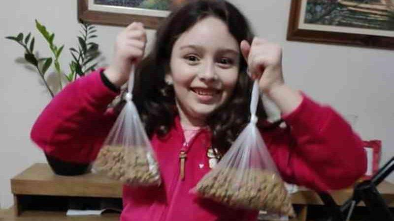 Menina de 7 anos distribui ração para cães de rua